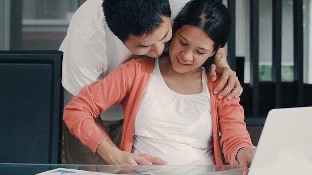 Giovane donna incinta asiatica che usando le annotazioni del computer portatile delle entrate e delle spese a casa. papà tocca la pancia della moglie mentre registra un bilancio, una tassa, un documento finanziario che lavora nel salotto di casa.