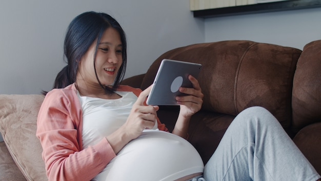 Giovane donna incinta asiatica che usando le informazioni di gravidanza di ricerca della compressa. la mamma si sente felice sorridente positivo e pacifico mentre si prende cura del suo bambino sdraiato sul divano nel salotto di casa.