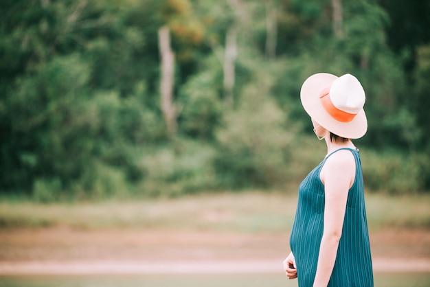 Giovane donna incinta asiatica felice che si distende e che gode della vita in natura