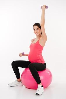 Giovane donna incinta che fa esercizio facendo uso della palla e delle teste di legno di forma fisica