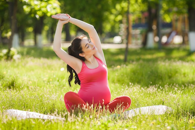 Giovane donna incinta che fa le esercitazioni di yoga.