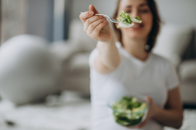 Giovane donna incinta che mangia insalata a casa