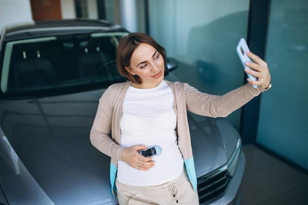 Giovane donna incinta che sceglie un'automobile in una sala d'esposizione dell'automobile