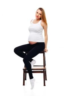 Giovane donna incinta che si siede su una sedia isolata su una priorità bassa bianca. vestito con una canotta bianca e pantaloni aderenti neri.