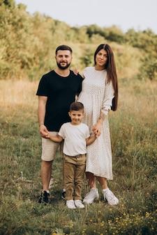 Giovane donna incinta con marito e figlio in una foresta