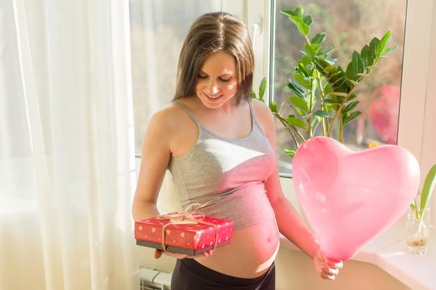 Giovane donna incinta felice con il contenitore di regalo e l'aerostato del cuore