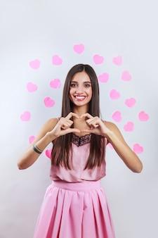 Giovane donna indiana abbastanza romantica del brunette che fa un gesto del cuore con le sue dita nella parte anteriore. concetto di san valentino