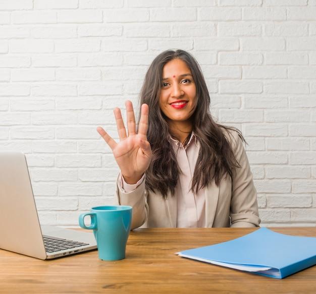 Giovane donna indiana all'ufficio che mostra il numero quattro, simbolo di conteggio, concetto di matematica
