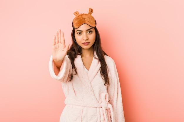 Giovane donna indiana che indossa un pigiama e maschera di sonno in piedi con la mano tesa che mostra il segnale di stop, impedendoti.