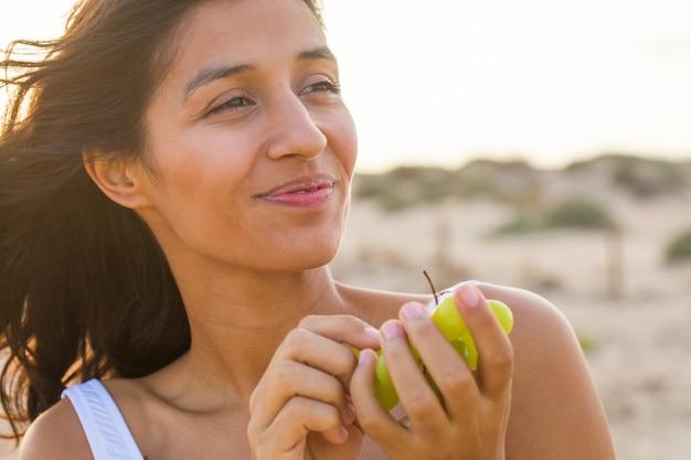 Giovane donna indiana che mangia frutta sulla spiaggia