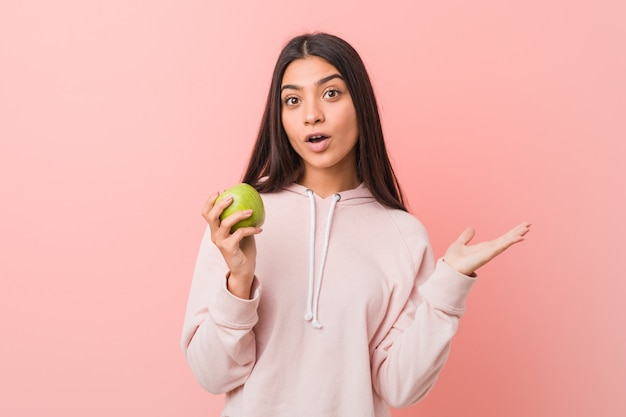 Giovane donna indiana che mangia una mela
