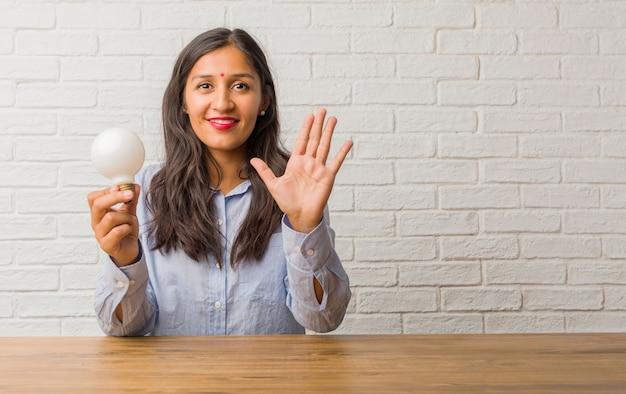 Giovane donna indiana che mostra numero cinque, simbolo del conteggio, concetto di matematica, sicuro e allegro. in possesso di una lampadina.