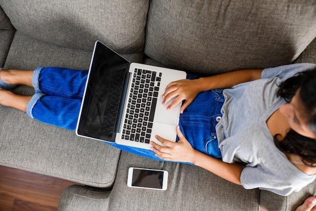 Giovane donna indiana che per mezzo del computer a casa