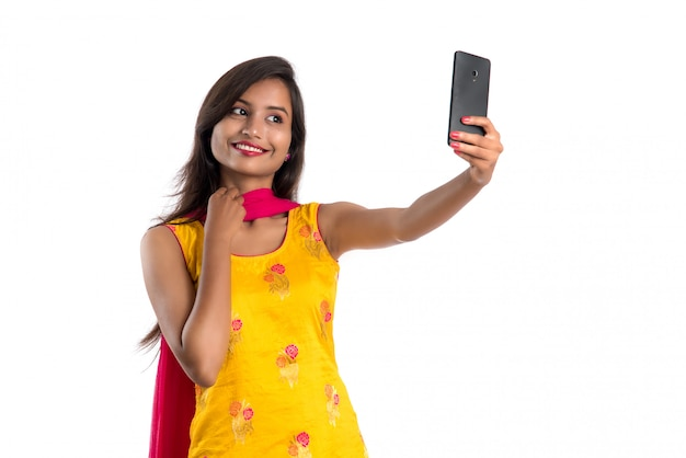 Giovane donna indiana che per mezzo di una compressa, di un telefono cellulare o di uno smartphone isolati su bianco