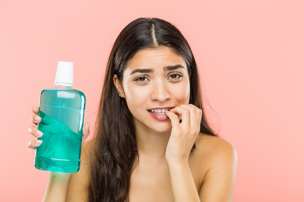 Giovane donna indiana che tiene una bottiglia di collutorio che morde le unghie, nervosa e molto ansiosa.