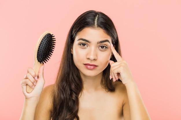 Giovane donna indiana che tiene una spazzola per i capelli che indica il suo tempio con il dito, pensando, messo a fuoco su un compito.