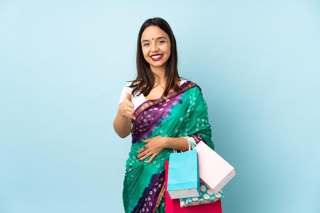Giovane donna indiana con borse della spesa si stringono la mano per chiudere un buon affare