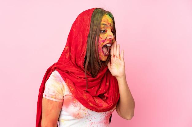 Giovane donna indiana con colorate polveri di holi sul viso sul muro rosa che grida con la bocca spalancata sul lato