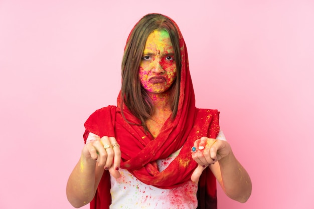 Giovane donna indiana con colorate polveri di holi sul viso sul muro rosa che mostra il pollice verso il basso con due mani