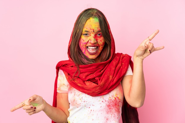 Giovane donna indiana con colorate polveri di holi sul viso sul muro rosa che punta il dito verso i laterali e felice