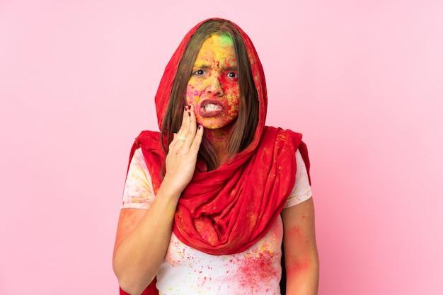 Giovane donna indiana con colorate polveri di holi sul viso sul muro rosa con mal di denti