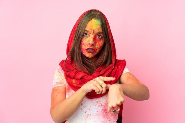 Giovane donna indiana con colorate polveri di holi sul viso sul muro rosa facendo il gesto di essere in ritardo