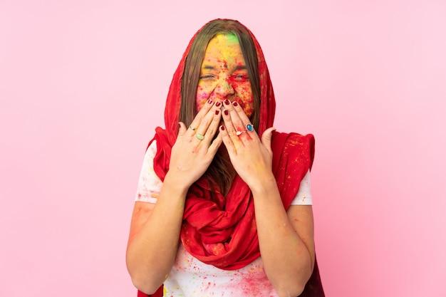 Giovane donna indiana con colorate polveri di holi sul viso sul muro rosa felice e sorridente che copre la bocca con le mani