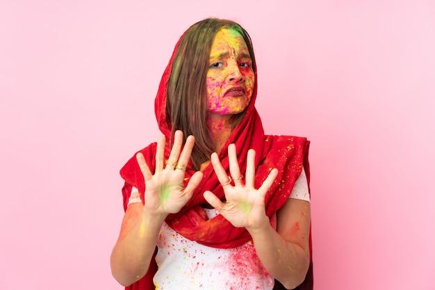 Giovane donna indiana con colorate polveri di holi sul viso sul muro rosa nervoso allungando le mani verso la parte anteriore