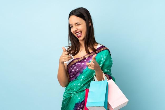 Giovane donna indiana con i sacchetti della spesa che indica la parte anteriore e sorridere