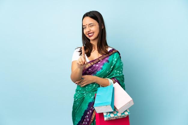 Giovane donna indiana con i sacchetti della spesa che mostra e che solleva un dito
