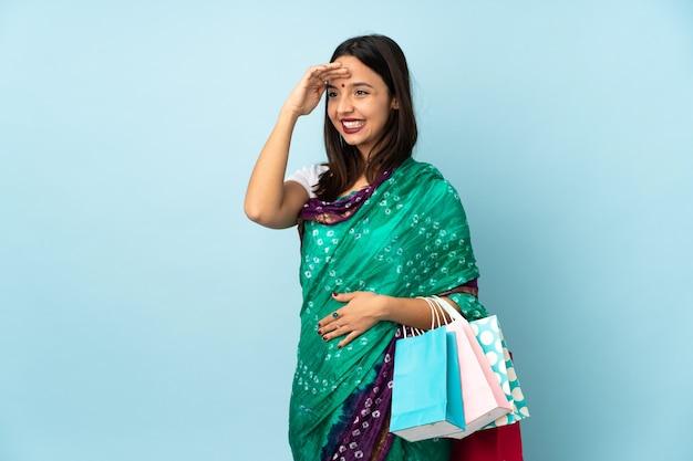 Giovane donna indiana con i sacchetti della spesa che saluta con la mano con l'espressione felice