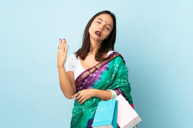 Giovane donna indiana con i sacchetti della spesa con l'espressione stanca e malata