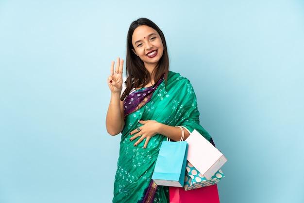 Giovane donna indiana con i sacchetti della spesa felici e contando tre con le dita