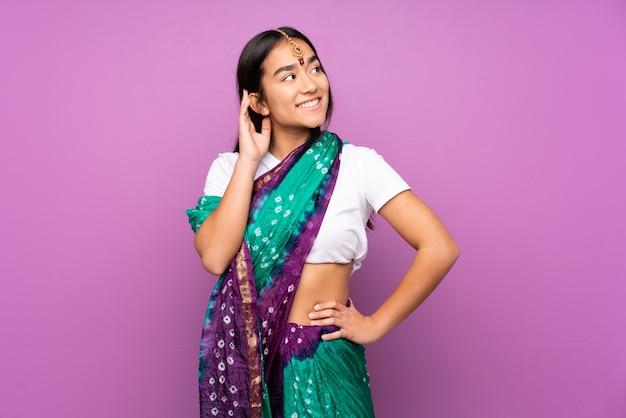 Giovane donna indiana con i sari sopra la parete isolata che pensa un'idea