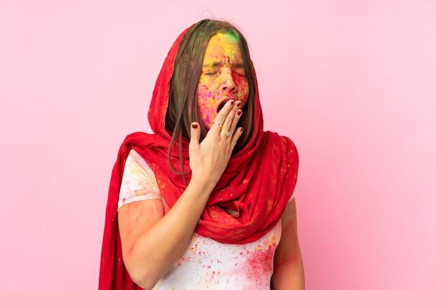 Giovane donna indiana con le polveri colorate di holi sul suo fronte isolato sulla parete rosa che sbadiglia e che copre bocca spalancata di mano