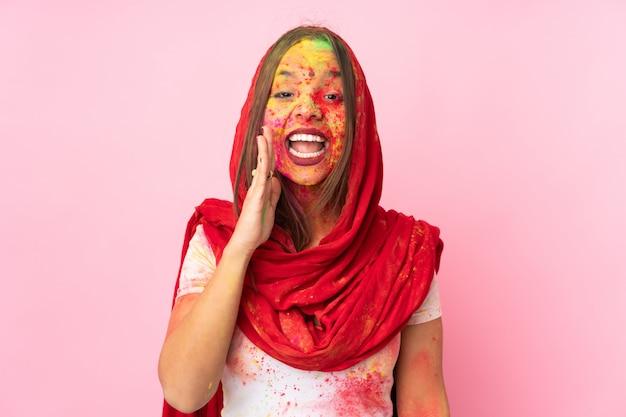 Giovane donna indiana con le polveri colorate di holi sul suo fronte sulla parete rosa che grida con la bocca spalancata