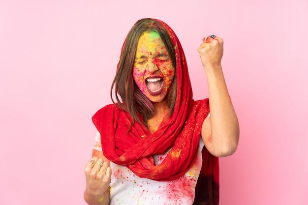 Giovane donna indiana con le polveri colorate di holi sul suo viso sulla parete rosa che celebra una vittoria