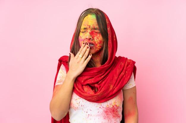 Giovane donna indiana con le polveri colorate di holi sul suo viso sulla parete rosa che sbadiglia e che copre la bocca spalancata con la mano