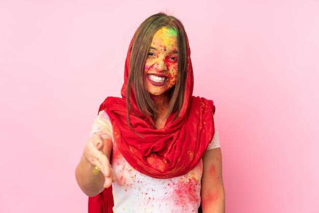 Giovane donna indiana con le polveri colorate di holi sul suo viso sulla parete rosa che stringe la mano
