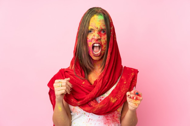 Giovane donna indiana con le polveri colorate di holi sul suo viso sulla parete rosa frustrata da una brutta situazione