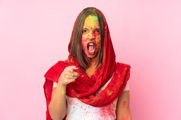 Giovane donna indiana con le polveri colorate di holi sul suo viso sulla parete rosa frustrata e che punta verso la parte anteriore