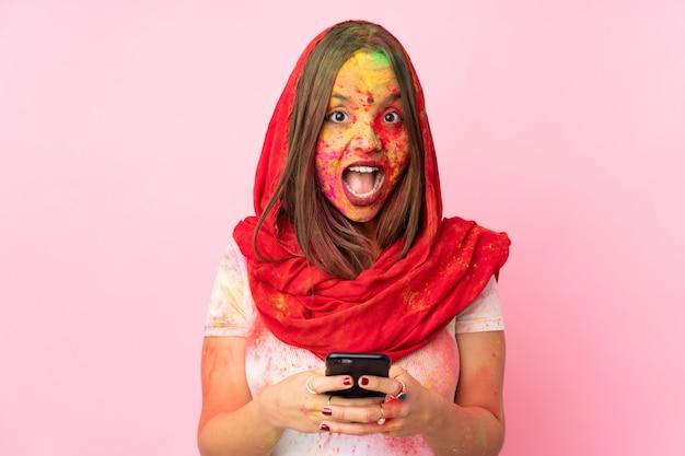 Giovane donna indiana con le polveri colorate di holi sul suo viso sulla parete rosa sorpresa e invio di un messaggio