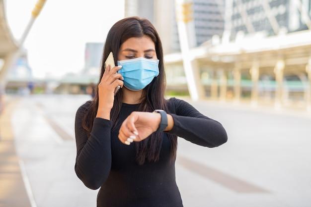 Giovane donna indiana con maschera parlando al telefono e controllo del tempo presso il ponte sullo skywalk