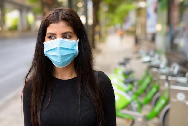 Giovane donna indiana con maschera per la protezione dall'epidemia di coronavirus alla stazione di servizio di biciclette pubbliche