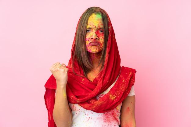 Giovane donna indiana con polveri colorate di holi sul viso sul muro rosa con espressione infelice