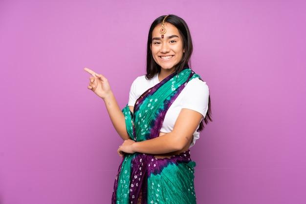 Giovane donna indiana con sari sul muro che punta il dito verso il lato