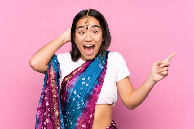Giovane donna indiana con sari sul muro sorpreso e puntando il dito verso il lato