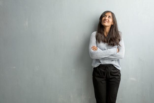 Giovane donna indiana contro una parete del grunge che osserva in su, pensando a qualcosa di divertente e avendo un'idea, concetto di immaginazione, felice ed emozionato