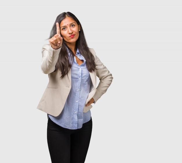Giovane donna indiana di affari che mostra numero uno, simbolo di conteggio, concetto di matematica, sicuro e allegro