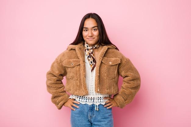 Giovane donna indiana di razza mista che indossa un cappotto corto di montone, sicura di tenere le mani sui fianchi.